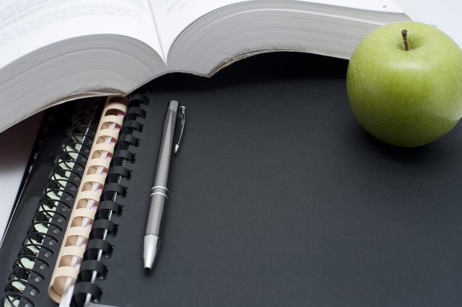 Education and learning background with a fresh healthy green apple alongside an open book with a pen and spiral binders
